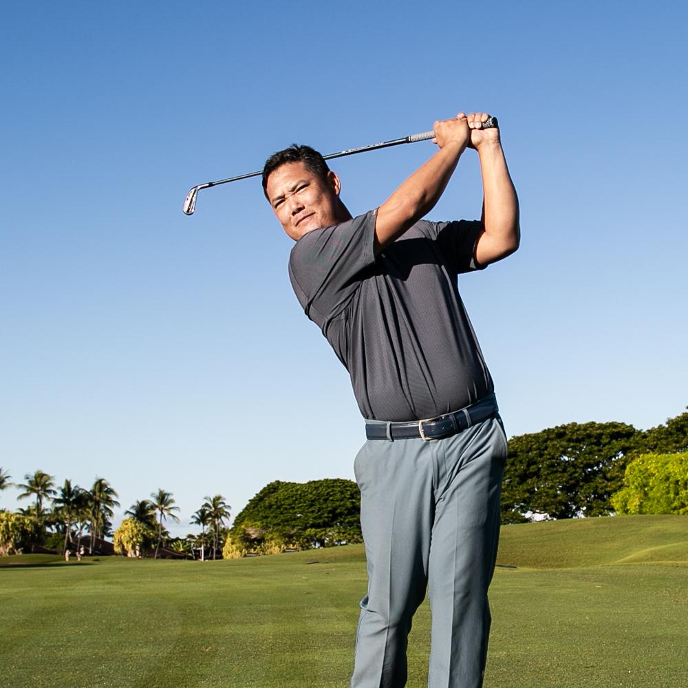 Golf pro Garratt Okamura swinging golf club