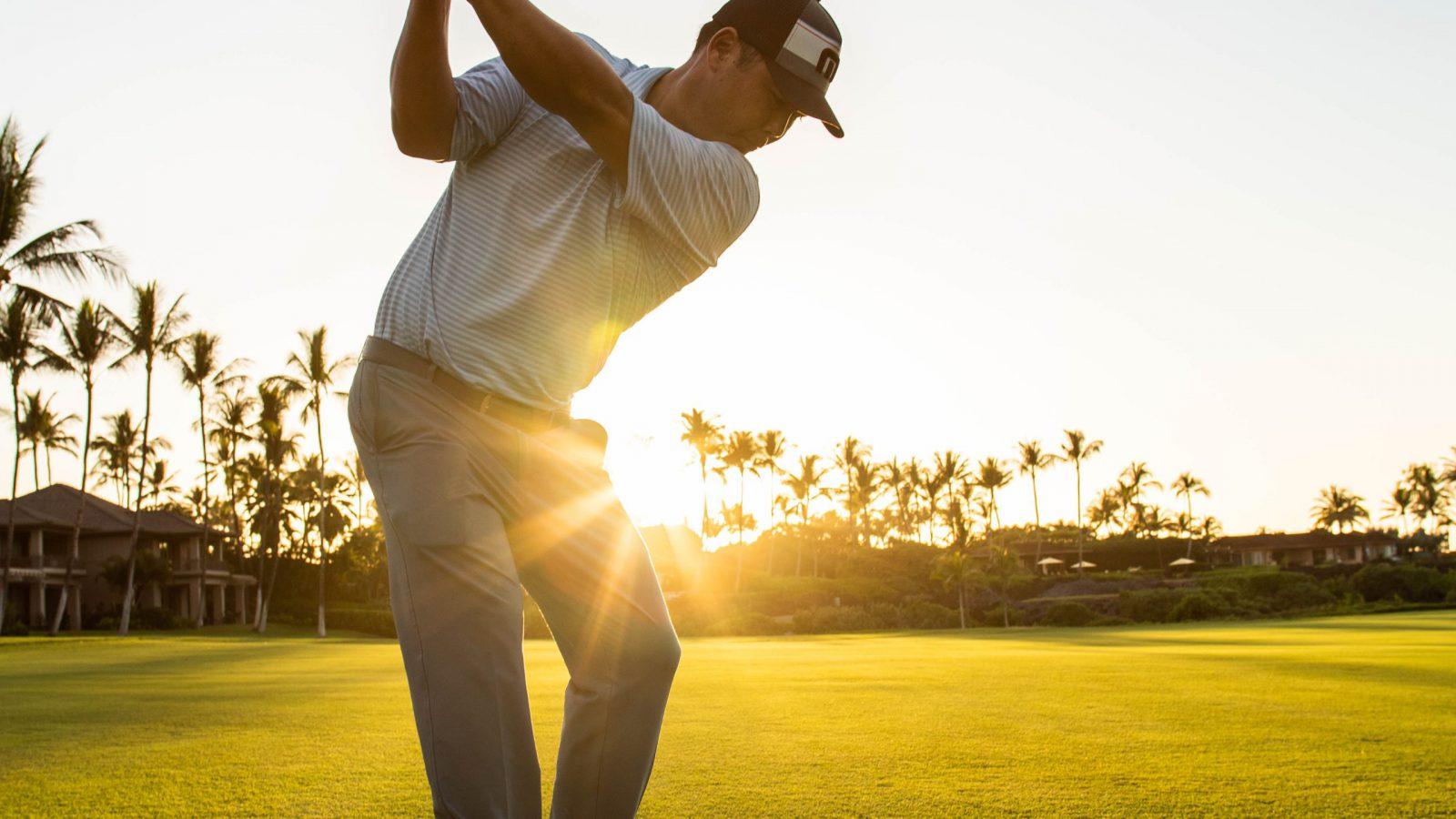 Golf Pro Garratt Okamura takes a swing a golf ball with setting sun in background