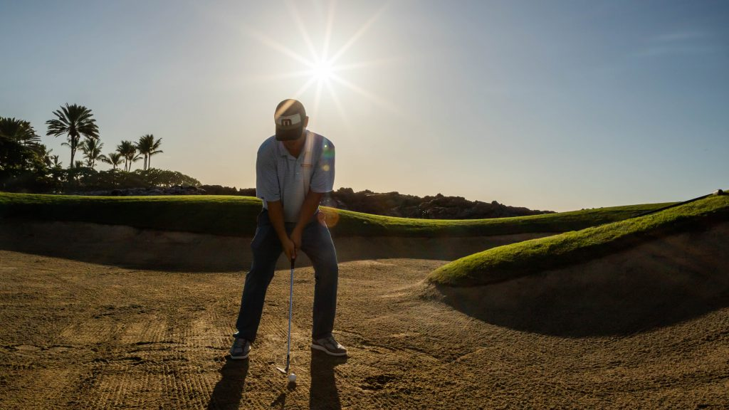 Pro Garratt Okamura chipping in a sand trap of golf course with sun behind