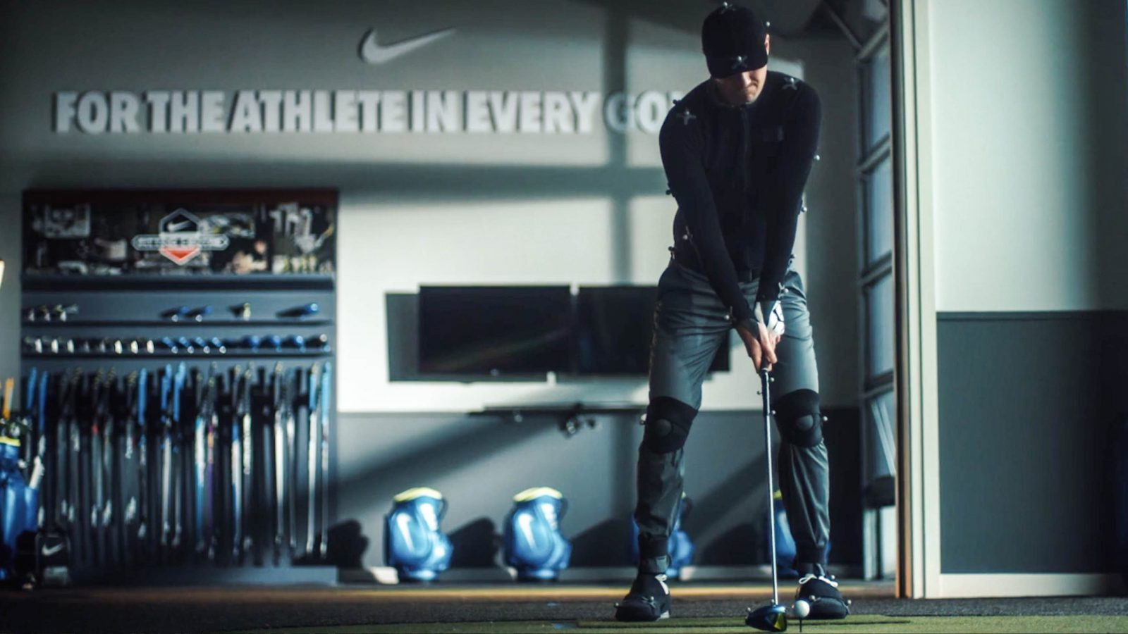 Male golfer with various technology attached to him prepares to hit a golf ball