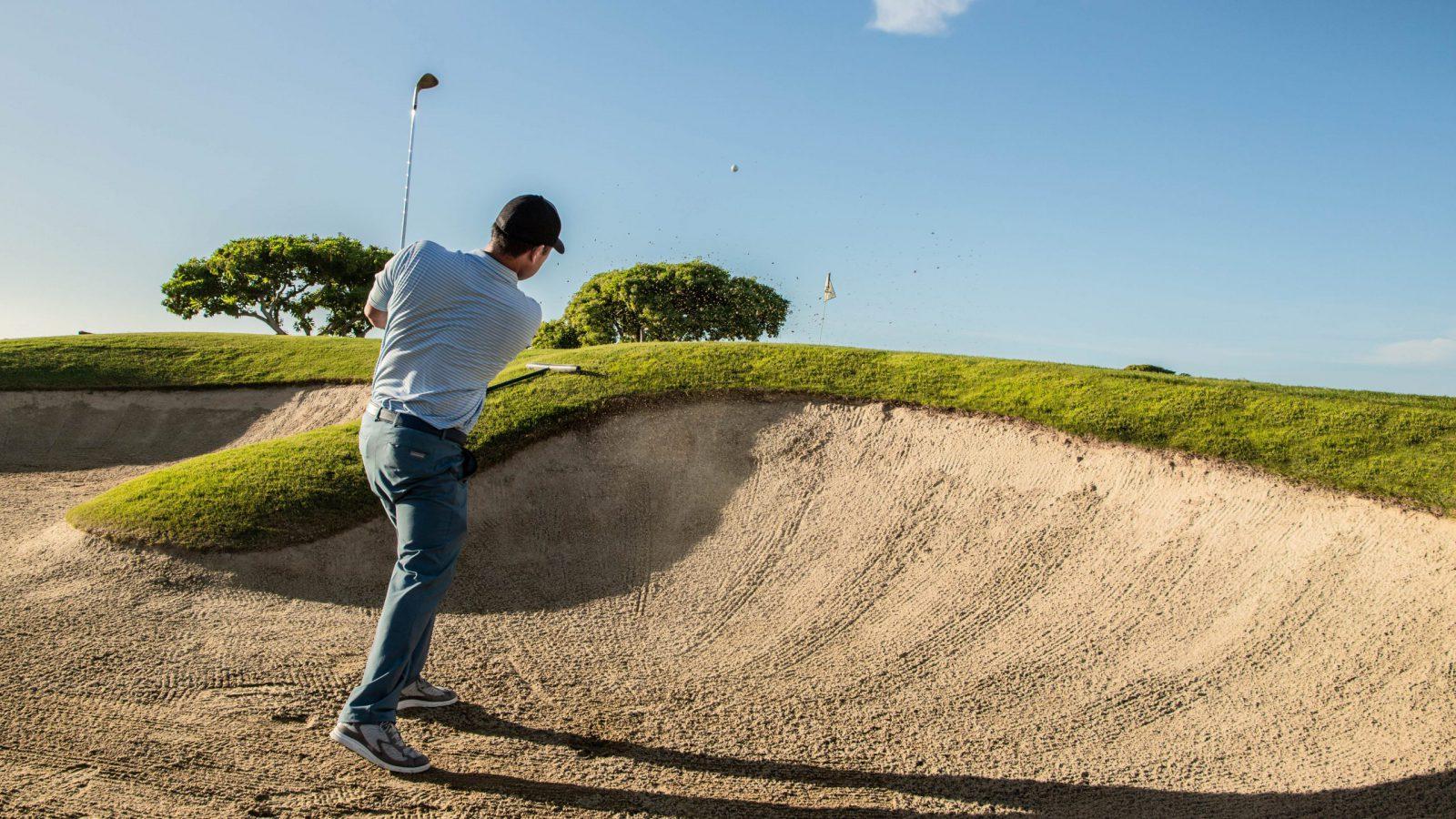 Golf Pro Garratt Okamura hits ball out of sand trap on course