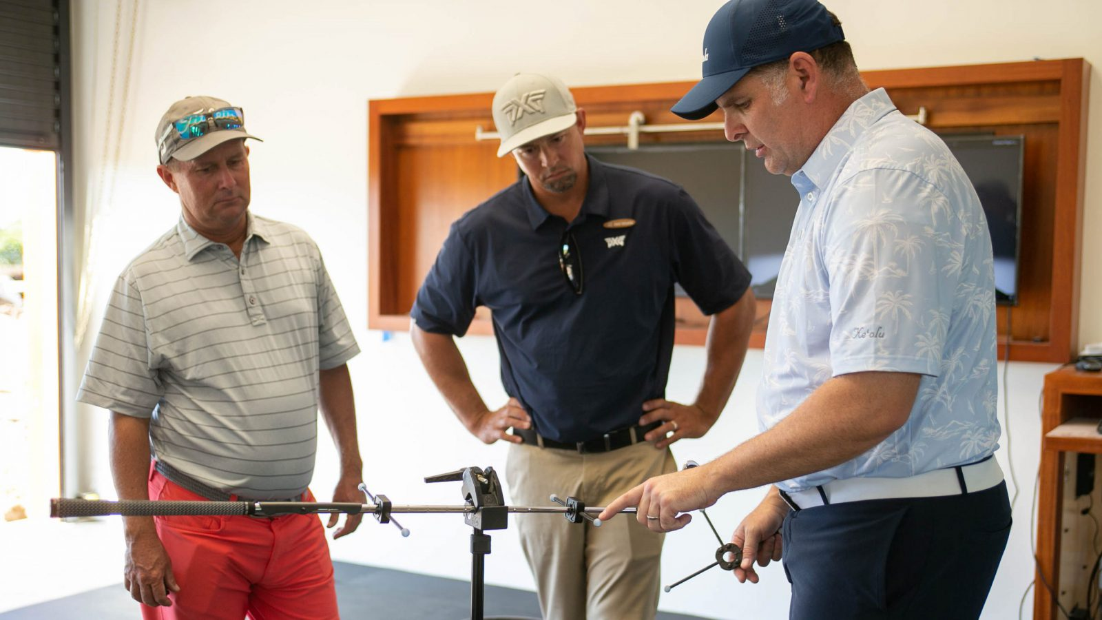 Golf Pro instructs golfers in a lesson