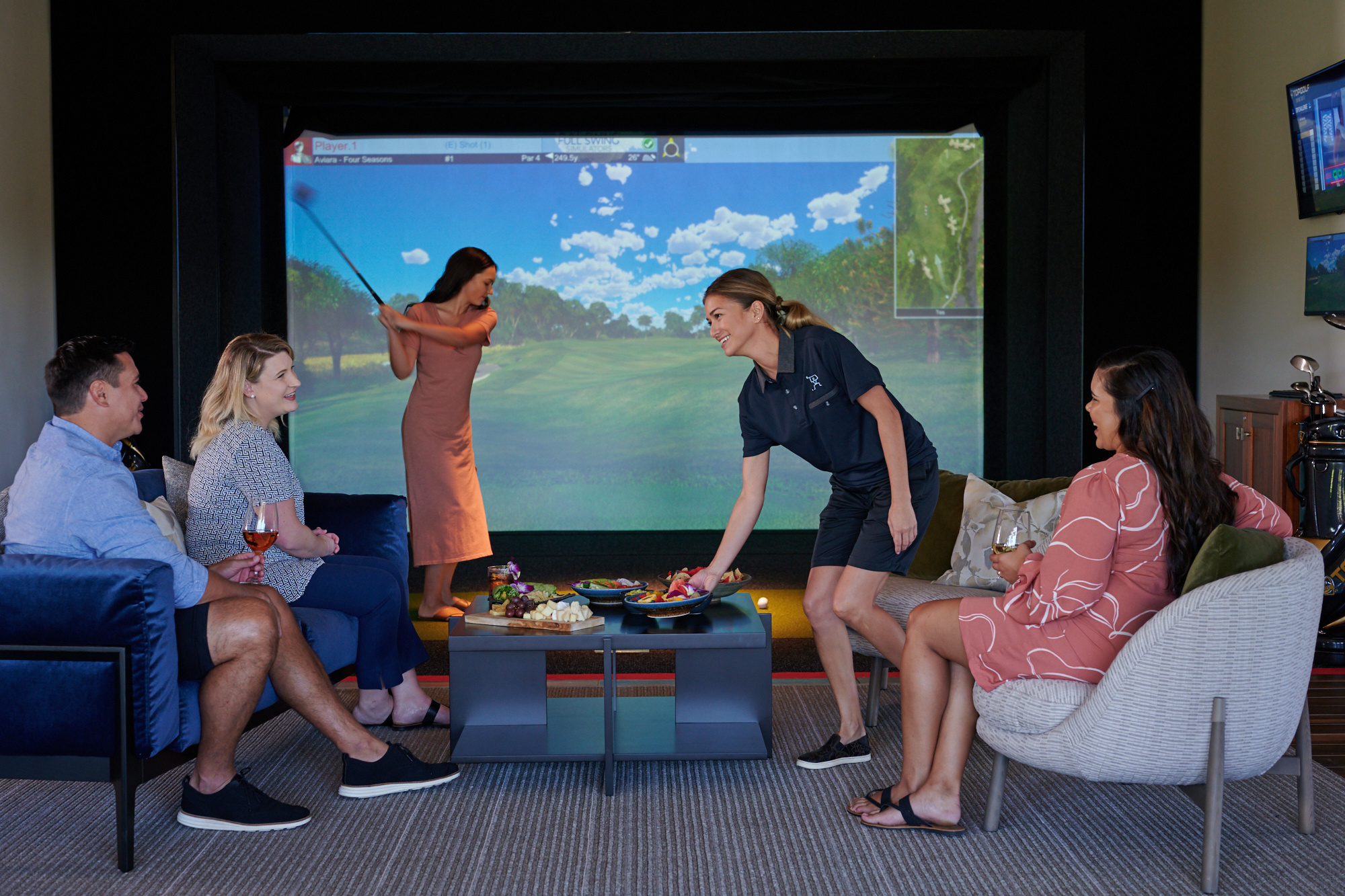 An employee places a colorful plate of food at a table in the center of the room while three guests thank her and one guest plays a virtual golf game.