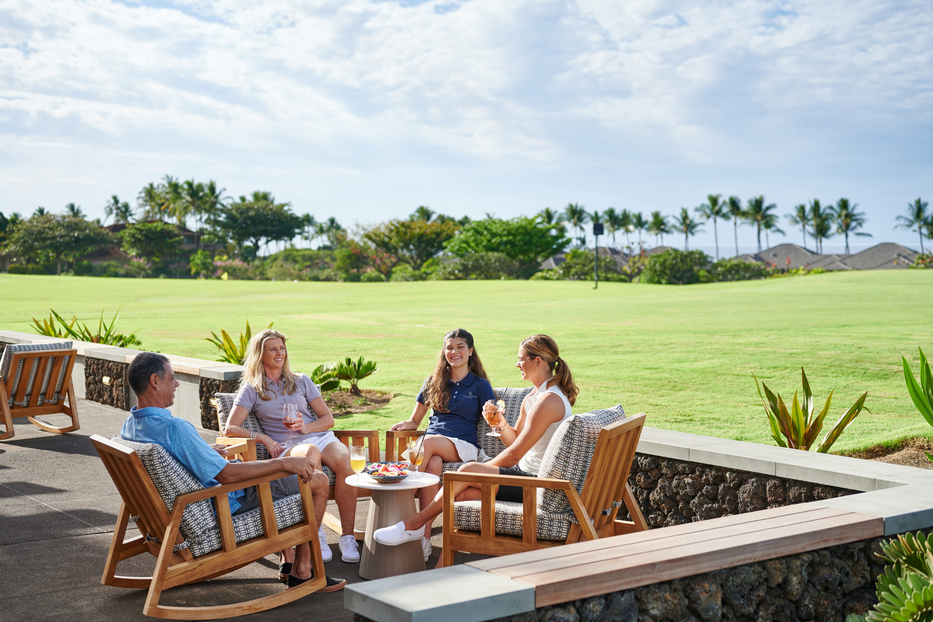 A family of four sits around a table in comfortable lounge chairs with a golf course in the background.