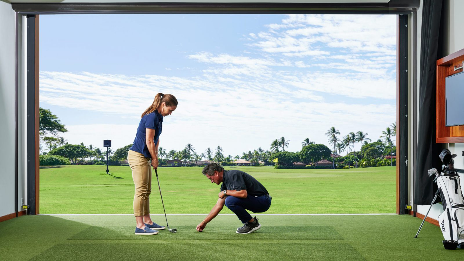 An instructor places a tee on the indoor golf turf while the person taking the lesson readies her swing.